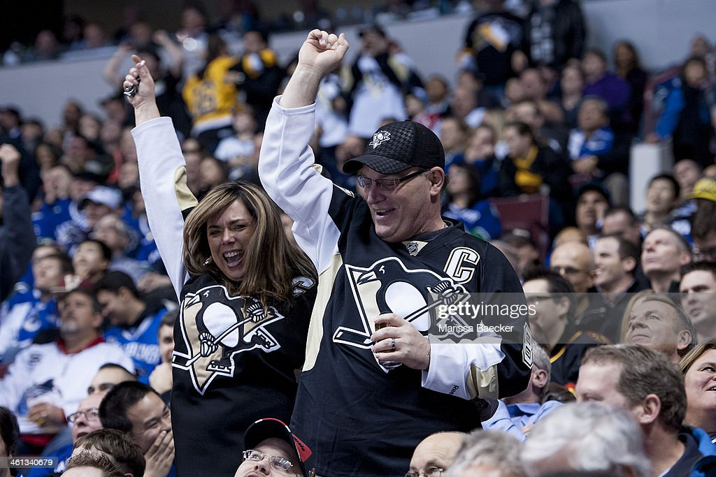 Pittsburgh Penguins fans celebrate the tying goal of the third period for the Pittsburgh Penguins against the Vancouver Canucks on January 7, 2014 at Rogers Arena in Vancouver, British Columbia, Canada.
