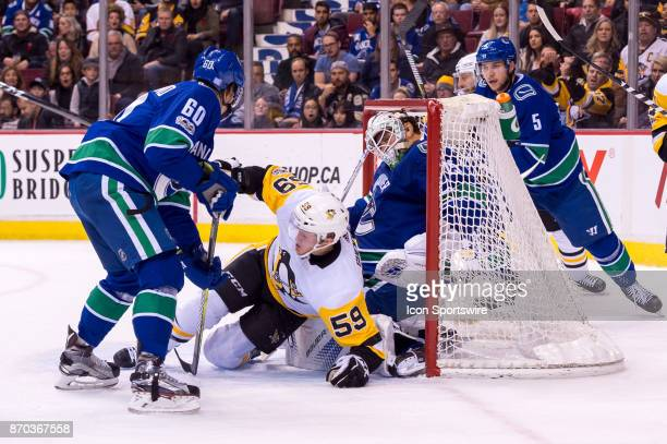 Pittsburgh Penguins Left Wing Jake Guentzel is checked into Vancouver Canucks Goalie Jacob Markstrom by Vancouver Canucks Center Markus Granlund...
