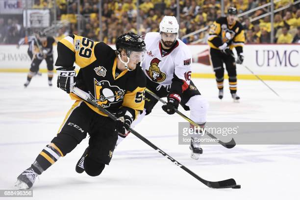 Pittsburgh Penguins Left Wing Jake Guentzel skates with the puck as Ottawa Senators left wing Clarke MacArthur defends during the first overtime...