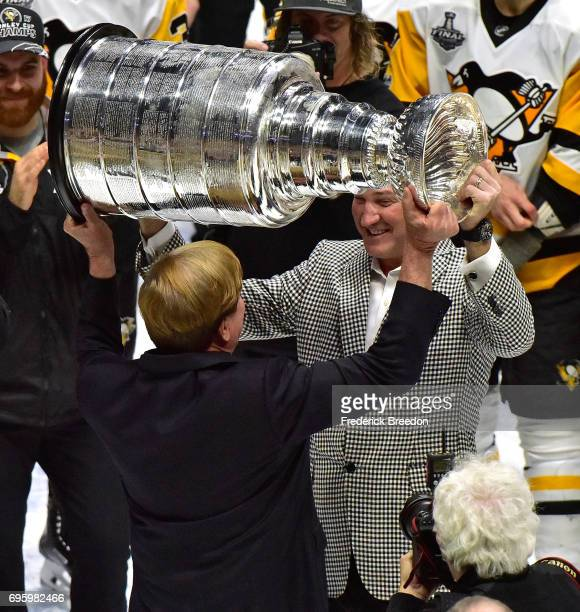 Pittsburgh Penguins owner Mario Lemieux hands the Stanley Cup Trophy to coowner Ron Burkle after defeating the Nashville Predators 20 in Game Six of...
