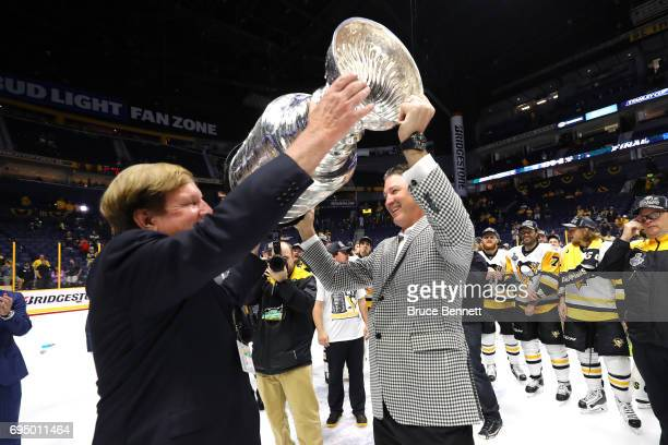 Pittsburgh Penguins owners Ronald Burkle and Mario Lemieux raise the Stanley Cup Trophy after they defeated the Nashville Predators 20 in Game Six of...