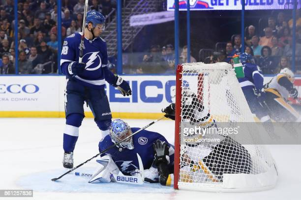 Pittsburgh Penguins right wing Bryan Rust slides into Tampa Bay Lightning goalie Andrei Vasilevskiy after his shot was defended by Tampa Bay...