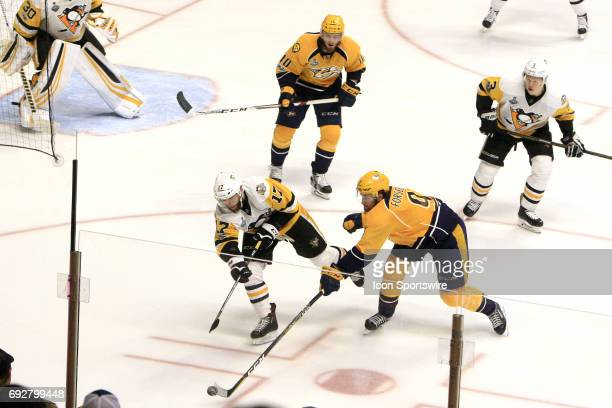 Pittsburgh Penguins right wing Bryan Rust tries to clear the puck over the stick of Nashville Predators left wing Filip Forsberg during Game 4 of the...