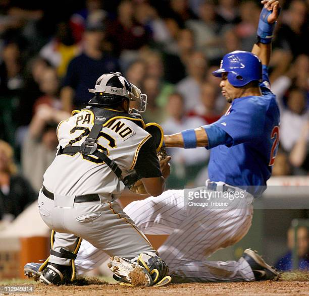Pittsburgh Pirates catcher Ronny Paulino makes the tag on Chicago Cubs' Derrek Lee at home in the seventh inning at Wrigley Field in Chicago Illinois...