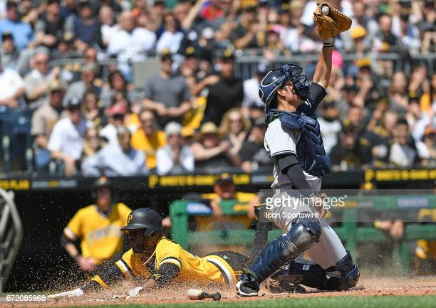 Pittsburgh Pirates right fielder Andrew McCutchen slides in safely for a run past New York Yankees catcher Kyle Higashioka in the third inning during...