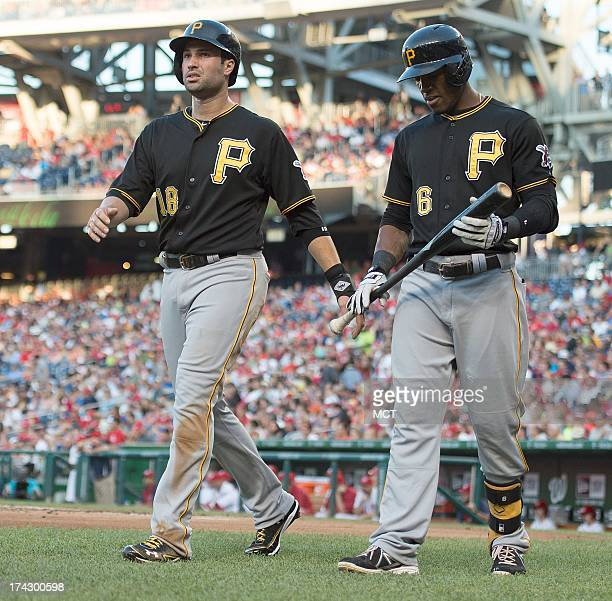 Pittsburgh Pirates second baseman Neil Walker left talks with left fielder Starling Marte after scoring against the Washington Nationals during the...