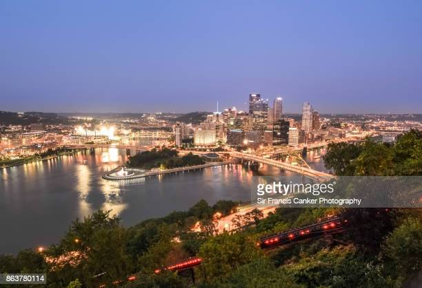 Pittsburgh skyline after sunset as seen from Mount Washington with Fort Pitt Bridge spanning the Monongahela River to the right and Fort Duquesne Bridge spanning the Allegheny River to the left and several skyscrapers in Pittsburgh, Pennsylvania