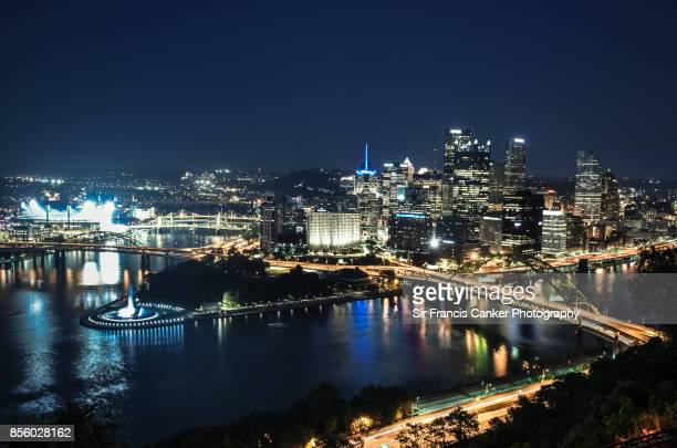 Pittsburgh skyline at late dusk as seen from Mount Washington with Fort Pitt Bridge spanning the Monongahela River to the right and Fort Duquesne Bridge spanning the Allegheny River to the left and several skyscrapers in Pittsburgh, Pennsylvania