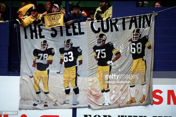 Pittsburgh Steelers fans wave their Terrible Towels near a sign depicting the Steelers 'Steel Curtain' defensive line of the 1970s as the Steelers...