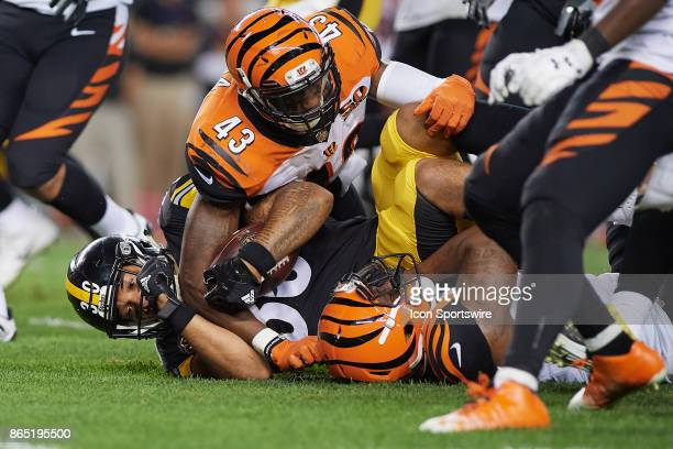 Pittsburgh Steelers running back James Conner is tackled by Cincinnati Bengals cornerback Darqueze Dennard and free safety George Iloka during an NFL...