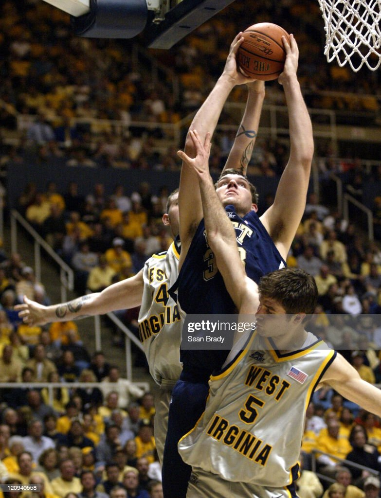 Pittsburgh's Aaron Gray goes up for 2 points against West Virginia's Kevin Pittsnogle and Johannes Herber during action at the WVU Coliseum in...