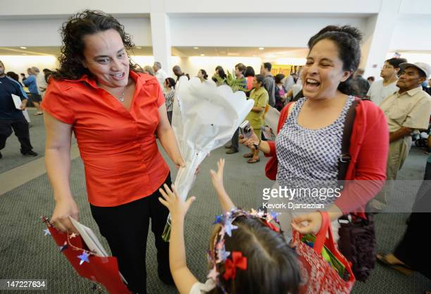 Pitzil AvilaCastellanos gives her aunt Hilda Alfaro flowers as her sister Betsy Castellanos looks on after Alfaro took the oath of citizensip after a...