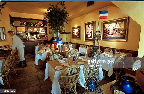 Pix of the interior of the restaurant with a small Eiffel Tower and French flag in the foregroundOwner Guy Levesque puttering around getting ready...