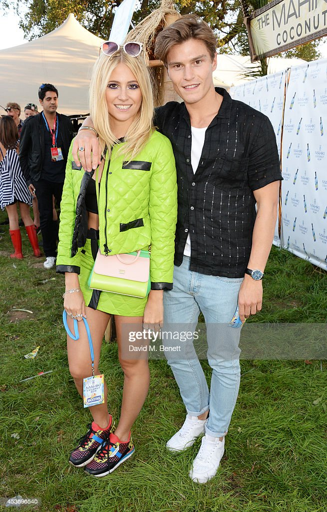 Pixie Lott (L) and Oliver Cheshire attend the Mahiki Rum Bar for the launch of the Mahiki Rum Family backstage during day 1 of the V Festival 2014 at Hylands Park on August 16, 2014 in Chelmsford, England.