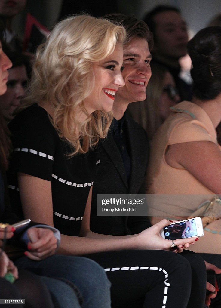 Pixie Lott (L) and Oliver Cheshire watch the Moschino cheap&chic show during London Fashion Week Fall/Winter 2013/14 at The Savoy Hotel on February 16, 2013 in London, England.