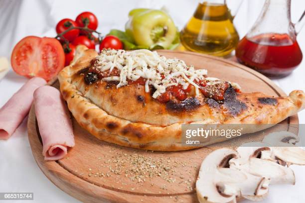 Pizza calzone on a white background with ingredients around