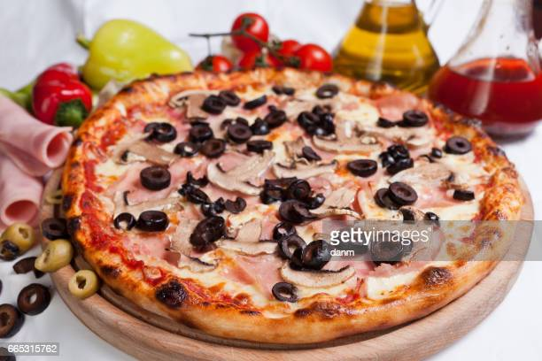 Pizza capriciosa on a white background with ingredients around
