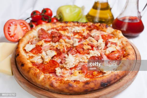 Pizza carnivora on a white background with ingredients around