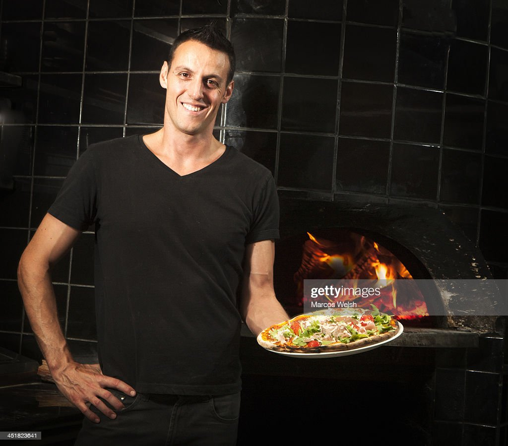 Pizza Chef holding wood fired cooked pizza : Stock Photo