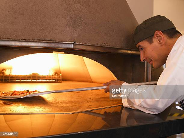 Pizza chef placing pizza in oven