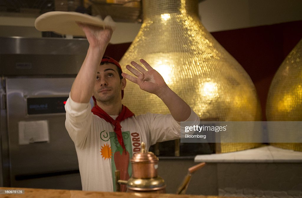 A pizza chef tosses dough into the air at an Eataly location in the Flatiron district of New York, U.S., on Wednesday, Feb. 6, 2013. Eataly is a high-end Italian food market/mall chain, owned by a partnership including Mario Batali, Lidia Bastianich and Joe Bastianich, which first opened in Turin, Italy, in 2007. Photographer: Scott Eells/Bloomberg via Getty Images