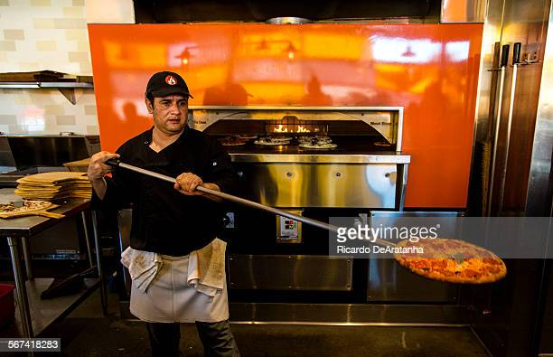 PASADENA CA FEBRUARY 21 2014 Pizza cook Jorge Agundez cq taking a pizza out of the oven at BLAZE PIZZA on East Colorado Blvd Friday February 21 2014
