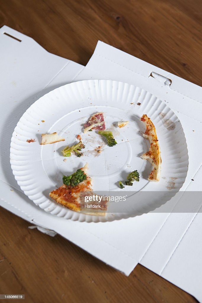 Pizza crusts on a paper plate in a cardboard box