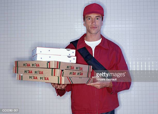 Pizza delivery man carrying stack of pizza boxes, portrait, close-up