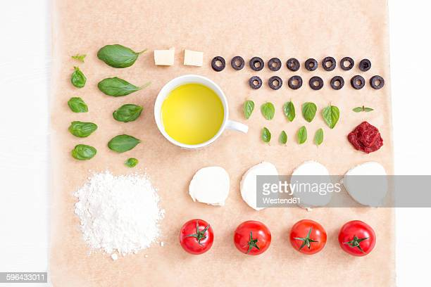 Pizza ingredients on baking paper