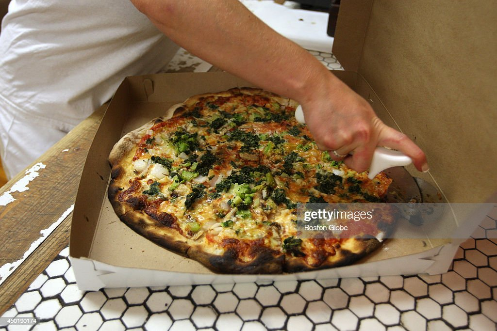 A pizza is prepared for a take out customer at Frank Pepe Pizzeria on Wooster Street in New Haven's Little Italy
