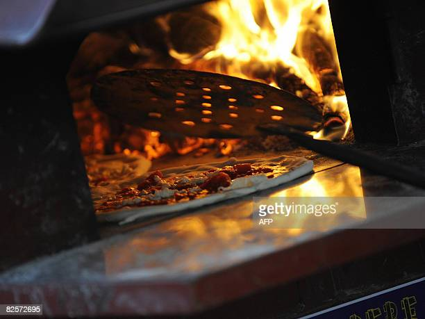 A pizza margherita bakes in the oven before it is given away for free in Dante square in downtown Naples on August 27 2008 Pizza chefs in Naples gave...