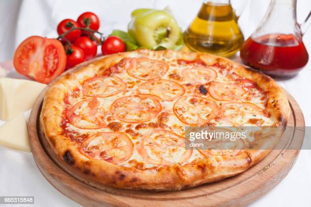 Pizza margherita on a white background with ingredients around
