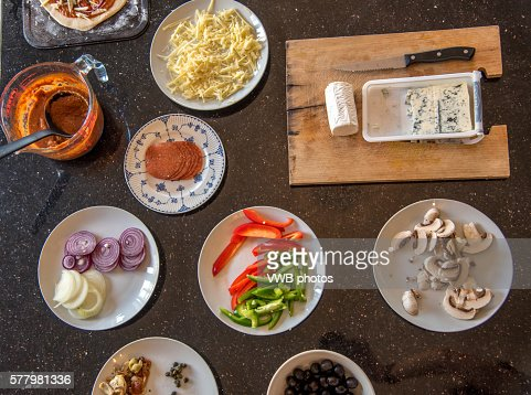 Pizza Party: A range of toppings laid out for a make your own pizza party, including tomato sauce, peppers, pepperoni, cheese, olives, onions and mushrooms
