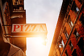 low angle view of pizza banner of restaurant in the city, urban scene.