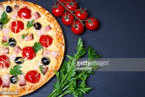 pizza with bacon, olives and tomato : Stock Photo