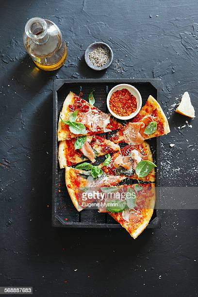 Pizza with prosciutto, basil and parmesan cheese