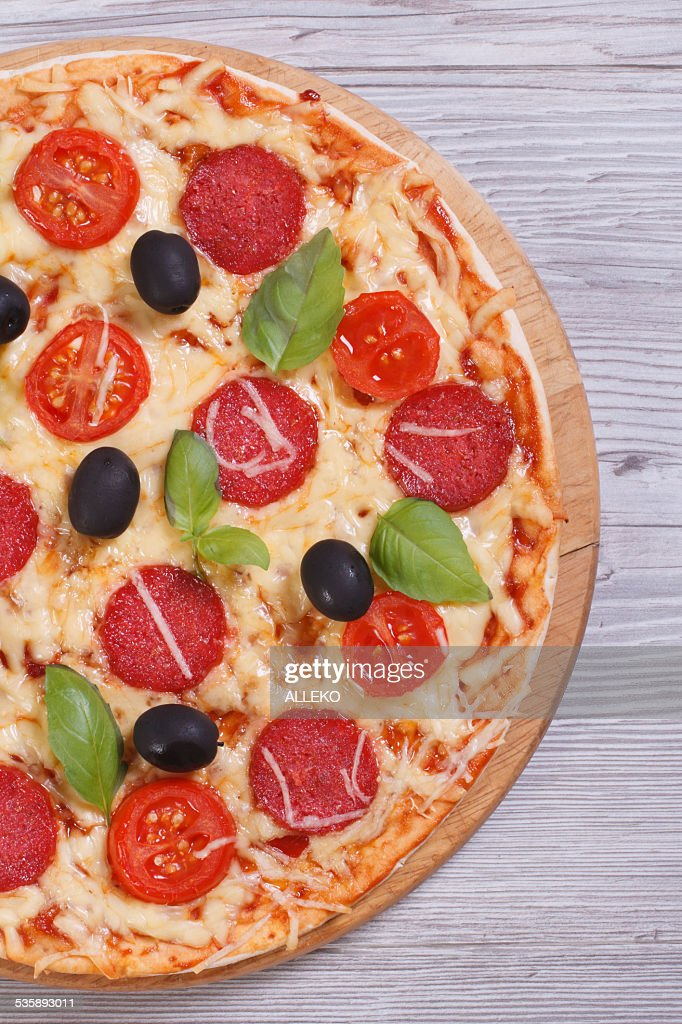 pizza with salami, tomato, cheese, olives and basil close-up : Stock Photo