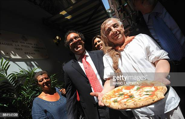 A pizzaiolo of the Brandi restaurant holds a pizza named after Queen Margherita of Savoy during a ceremony to celebrate the 120th anniversary of the...