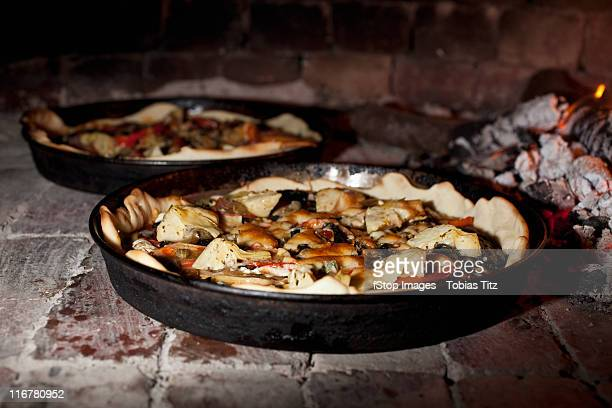 Pizzas cooking in a stone oven
