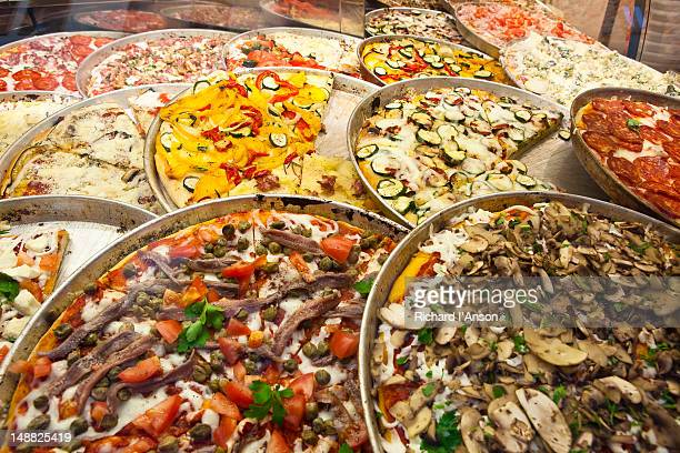Pizzas displayed on restaurant counter.