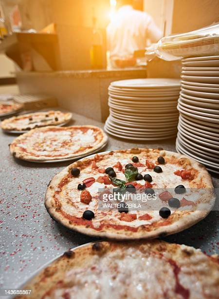 Pizzas on counter in kitchen