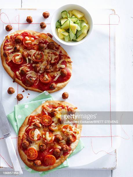 Pizzas with tomatoes and sausage