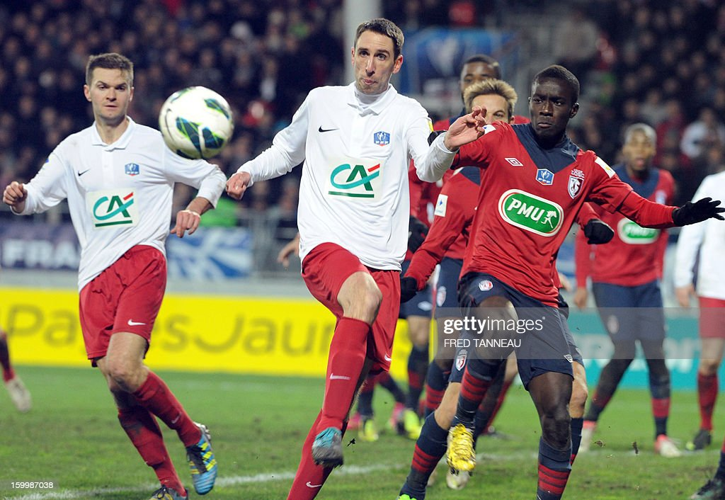 Plabennec's French defender Jean-Michel Abiven (C) vies with Lille's Senegalese midfielder Idrissa Gueye during the French Cup football match Plabennec vs Lille on January 24, 2013 in Brest, western of France. AFP PHOTO / FRED TANNEAU