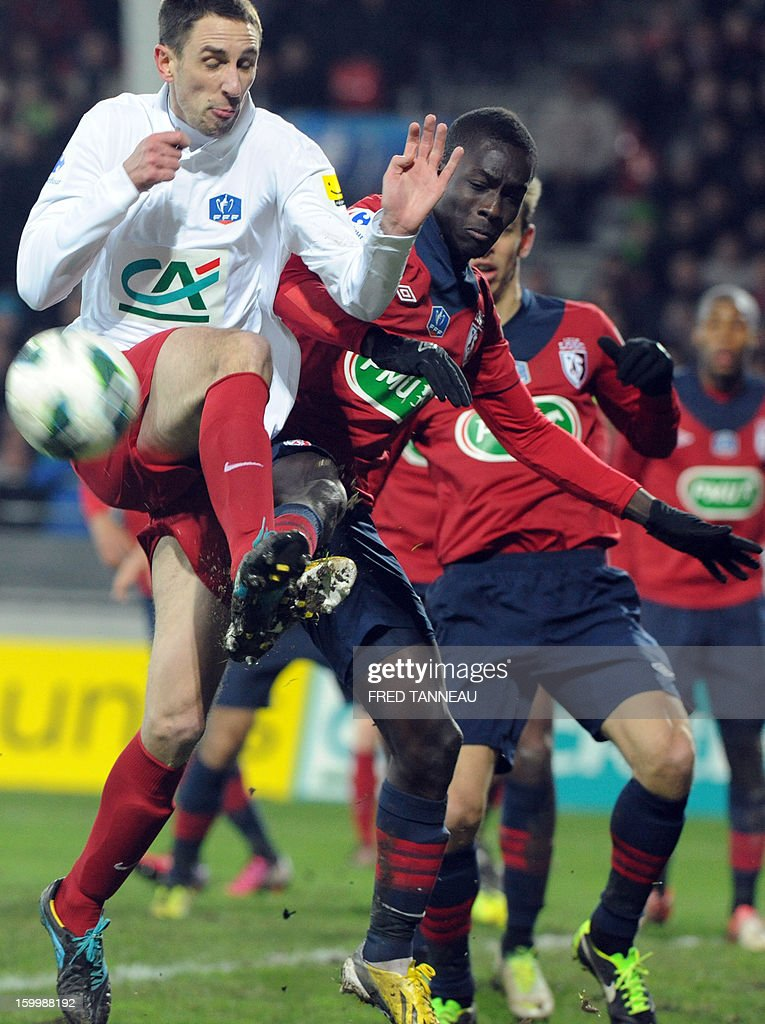 Plabennec's French defender Jean-Michel Abiven (C) vies with Lille's Senegalese midfielder Idrissa Gueye during the French Cup football match Plabennec vs Lille on January 24, 2013 in Brest, western of France.