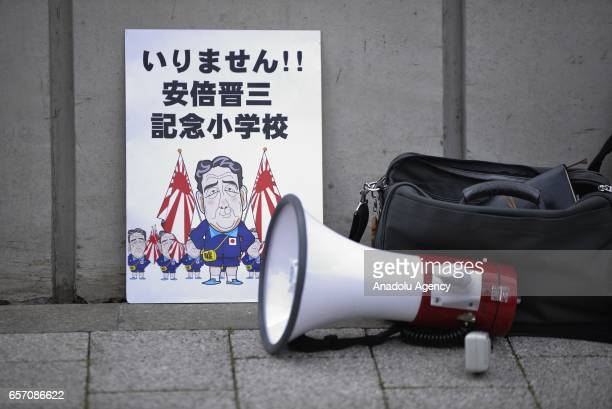 A placard against Japanese Prime Minister Shinzo Abe is seen as Yasunori Kagoike head of the Moritomo Gakuen group gives sworn testimony in the Diet...