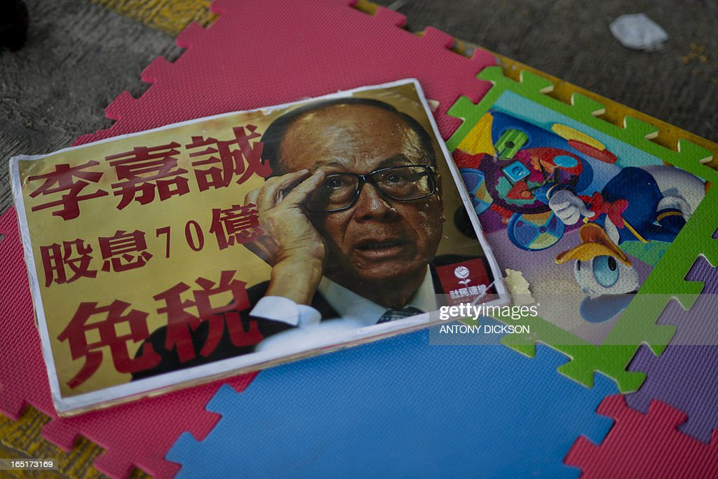 A placard bearing a photograph of tycoon Li Ka-shing lies on the ground as dock workers and their supporters gather at the Kwai Chung HIT container terminal during a strike, asking for better wages in Hong Kong on April 1, 2013. The dock workers, who work in one of the world busiest container ports in the world, claim their wages had not gone up in 15 years. HIT, which operates 12 berths, is a unit of tycoon Li's Hutchison Port Holdings Trust -- part of the vast empire owned by Asia's richest man, whose firms control about 70 percent of the city's port traffic. The placard states that Li's stock dividend is 7 billion Hong Kong dollars and the dividend is tax exempt. AFP PHOTO / Antony DICKSON