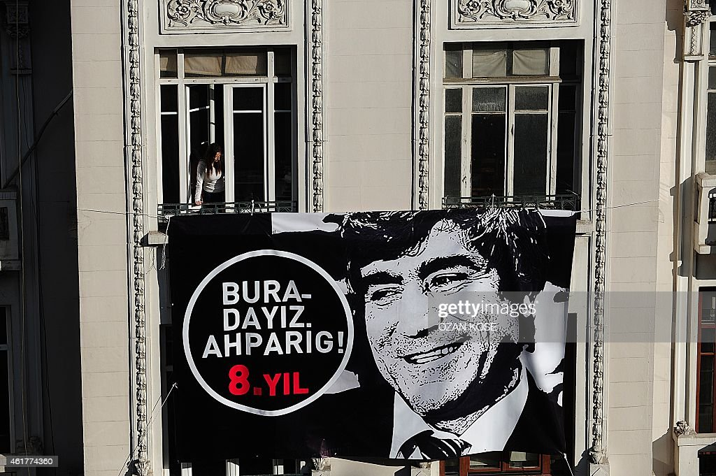 A placard bearing a picture of slain journalist <a gi-track='captionPersonalityLinkClicked' href=/galleries/search?phrase=Hrant+Dink&family=editorial&specificpeople=741548 ng-click='$event.stopPropagation()'>Hrant Dink</a> is hanged on the facade of Armenian newspaper 'Agos' while a woman looks out the crowd during a commemoration ceremony for Dink, in Istanbul, on January 19, 2015. Turkish riot police were out in force on Monday as large crowds massed in Istanbul to demand justice for a prominent Turkish Armenian journalist murdered eight years ago. <a gi-track='captionPersonalityLinkClicked' href=/galleries/search?phrase=Hrant+Dink&family=editorial&specificpeople=741548 ng-click='$event.stopPropagation()'>Hrant Dink</a>, one of the most prominent voices of Turkey's shrinking Armenian community, was killed by a gunman on January 19, 2007. The 52-year-old Dink, a prominent member of Turkey's tiny Armenian community, campaigned for reconciliation but was hated by Turkish nationalists for calling the World War I massacres of Armenians a genocide. AFP PHOTO /OZAN KOSE