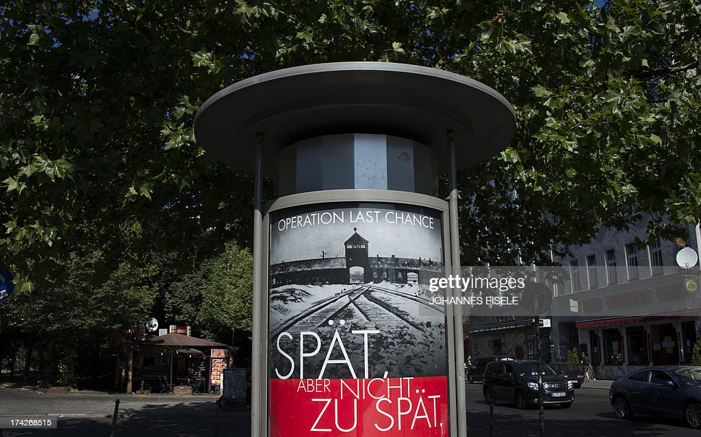 A placard featuring a black-and-white photograph of the Auschwitz-Birkenau death camp and the tagline: 'Late but not too late' as a campaign of Nazi-hunting Simon Wiesenthal Center seeking information on the last perpetrators of the Holocaust still at large nearly 70 years on, is pictured on July 23, 2013 in Berlin. AFP PHOTO / JOHANNES EISELE