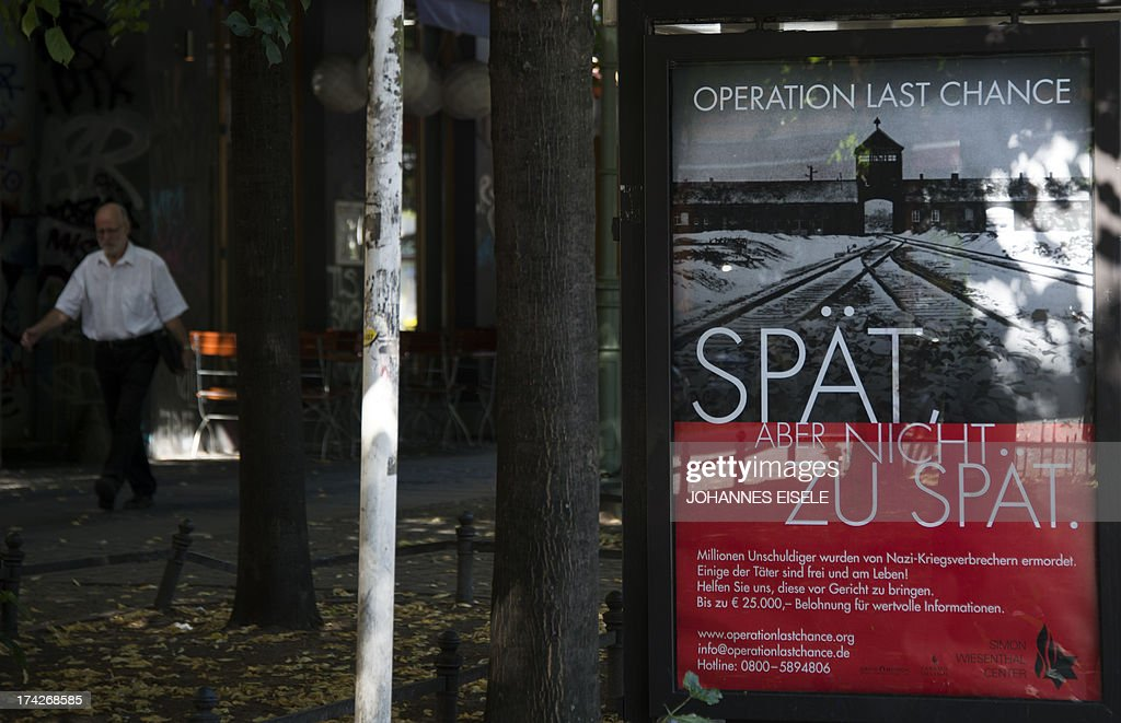 A placard (R) featuring a black-and-white photograph of the Auschwitz-Birkenau death camp and the tagline: 'Late but not too late' as a campaign of Nazi-hunting Simon Wiesenthal Center seeking information on the last perpetrators of the Holocaust still at large nearly 70 years on, is pictured on July 23, 2013 in Berlin. AFP PHOTO / JOHANNES EISELE