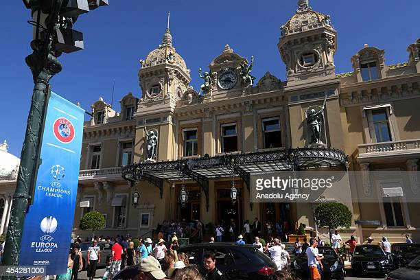 Placard is seen as people walk past at the street prior to the UEFA Champions League draw in Monaco on August 27 2014 The 32 clubs 22 of which...